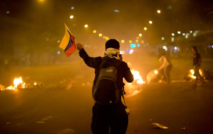 An anti-government demonstrator in the Altamira neighborhood of Caracas, Venezuela, Friday, February 21, 2014 (AP Photo/Rodrigo Abd)