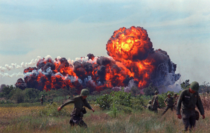 A napalm strike erupts in a fireball near US troops on patrol in South Vietnam. 1966. (AP Photo)