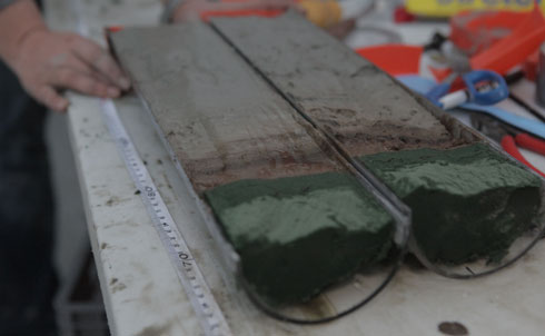 """A grad student splits one of the cores lengthwise and lays it out on deck. That's when we see it clearly: separating the gray and brown layers—and looking remarkably like chocolate parfait—is a thick line of black gunk. """"That's not normal,"""" marine geochemist David Hollander declares.    Credit: Jacqueline Soohen and Big Noise Films"""