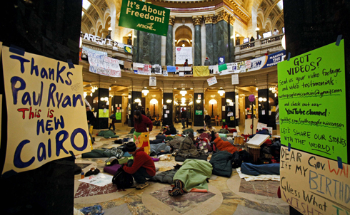 From the beginning of the opposition to Walker's bill, the State Capitol served as the center of the protests, and Wisconsin's long history of keeping the building open to all allowed for a truly democratic airing of dissent. After Walker threatened to restrict access to the building, protesters began camping out in the rotunda to ensure that their voices would be heard, paving the way for tactics that would later be used in the fall's Occupy Wall Street movement.  Credit: AP Images