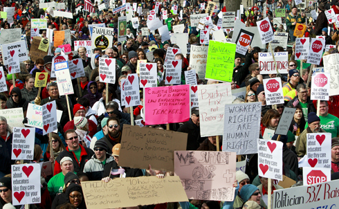 """On Valentine's Day, February 14, the first stirrings of protest began as high school students staged a walk-out and University of Wisconsin at Madison students sent valentines to Walker reading """"We ♥ UW: Don't Break My ♥.""""  Credit: AP Images"""