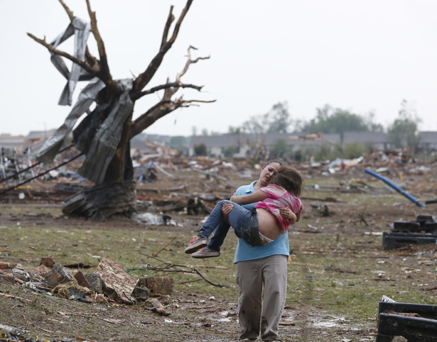 A woman carries her child after the tornado in Moore, OK