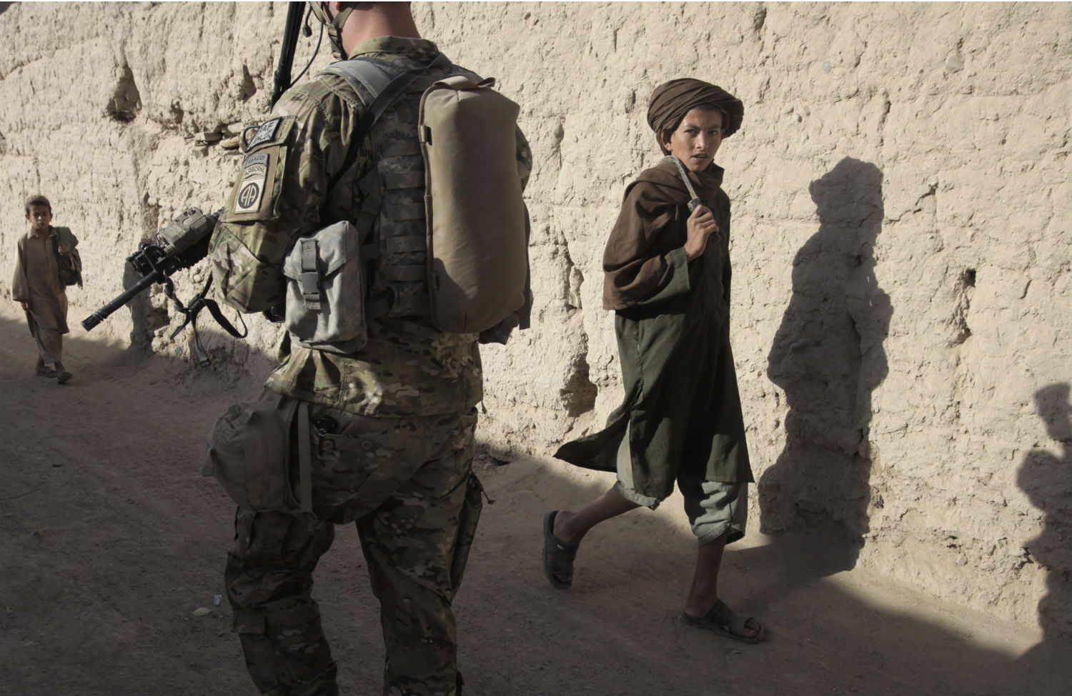 A-local-boy-looks-at-US-Army-soldiers-as-they-conduct-a-morning-patrol-through-the-village-of-Kowall-in-Arghandab-District-July-11-2010.-ReutersBob-Strong