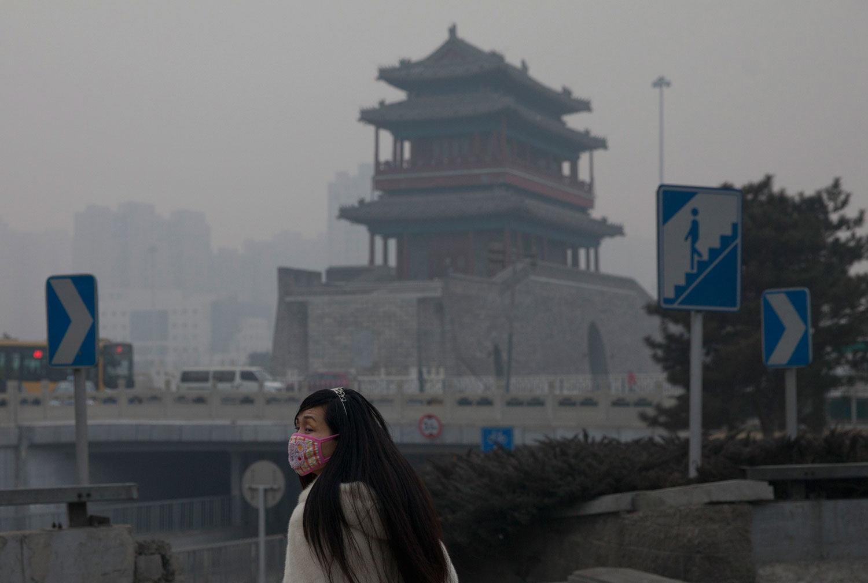 A-woman-wears-a-mask-as-she-walks-under-smog-in-Beijing-China.-AP-PhotoAlexander-F.-Yuan