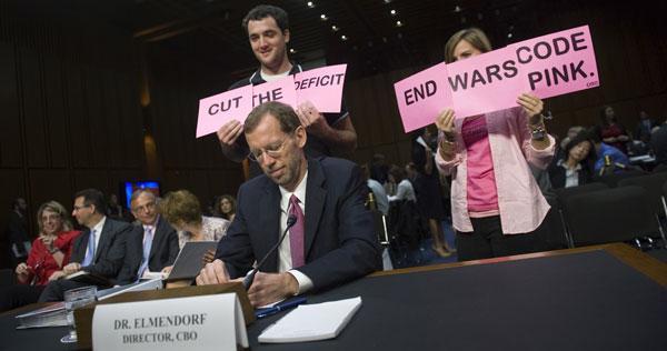 Code Pink protests behind CBO head Douglas Elmendorf