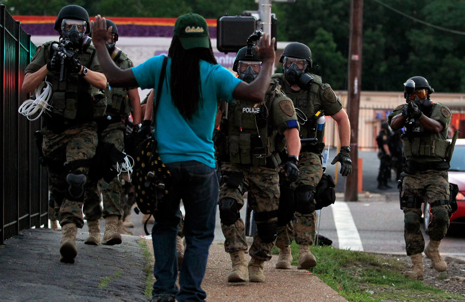 Police-wearing-riot-gear-walk-toward-a-man-with-his-hands-raised-in-Ferguson-MO
