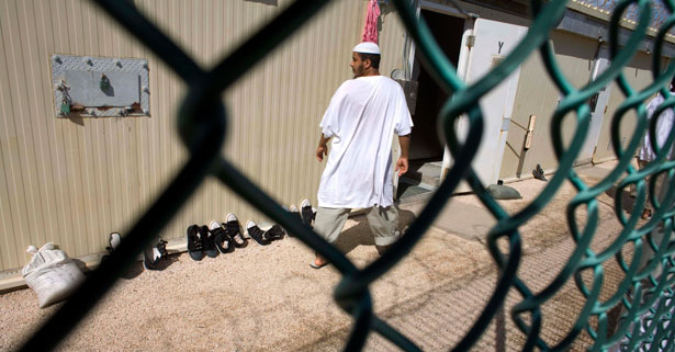 pemA-Guantanamo-detainee-walks-past-a-cell-block-at-Camp-4-detention-facility-Nov.-18-2008.-AP-PhotoBrennan-Linsleyemp