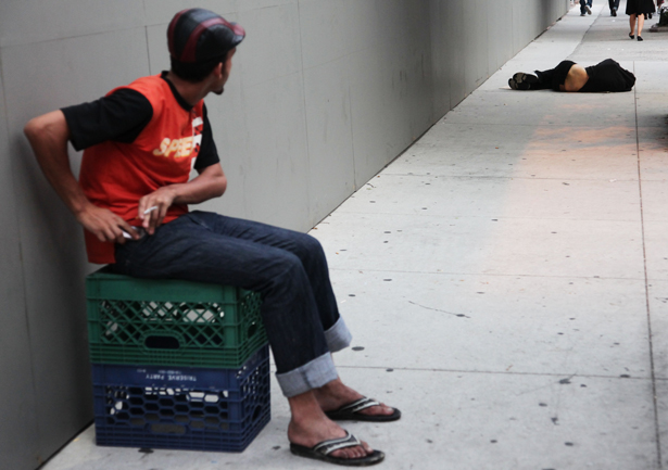 A-destitute-man-sleeps-on-the-sidewalk-under-a-holiday-window-at-Blanc-de-Chine-Wednesday-Nov.-20-2013-in-New-York.-AP-Images