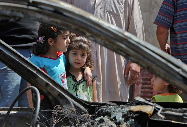Zahra-Naaim-4-center-and-Balqes-Youssif-6-left-stand-next-to-a-destroyed-vehicle-in-the-Shiite-stronghold-of-Sadr-City-in-Baghdad-Iraq.-AP-Photo