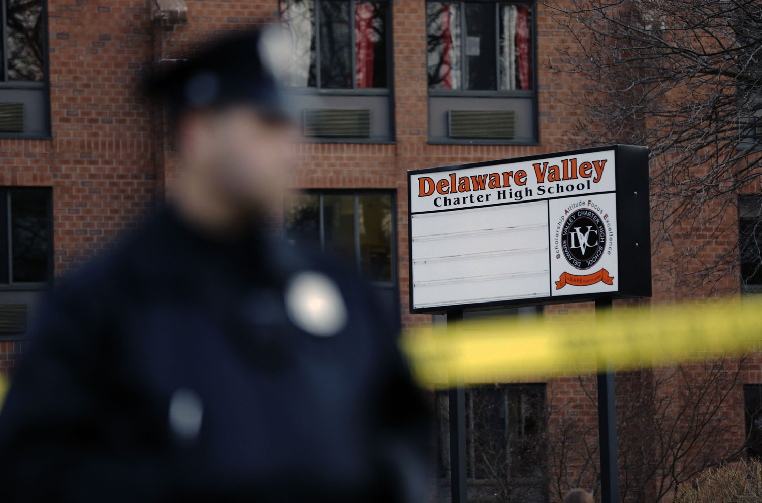 A-police-stands-by-caution-tape-at-the-Delaware-Valley-Charter-School-Friday-in-Philadelphia-where-two-students-were-shot-on-Jan.-17-2014.-AP-PhotoMatt-Rourke