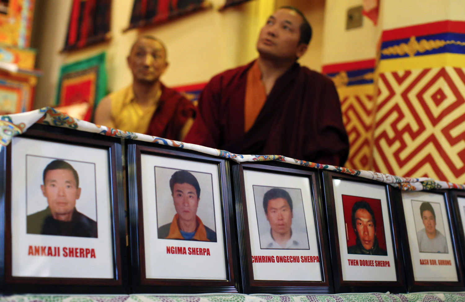 Pictures-of-Sherpa-members-are-displayed-while-Buddhist-monks-hold-a-prayer-service-for-those-killed