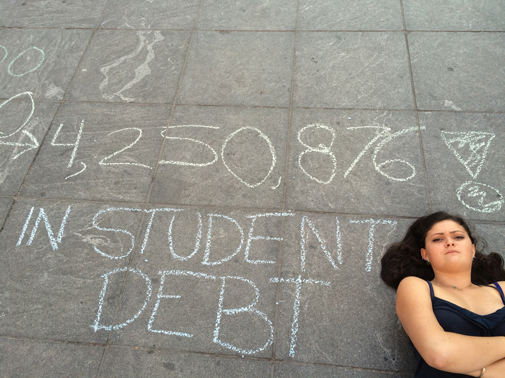 A-student-protestor-poses-with-chalk-graffiti