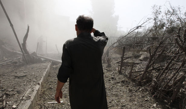 A-man-inspects-a-site-hit-by-what-activists-said-were-missiles-fired-by-Syrian-Air-Force-fighter-jets-loyal-to-President-Bashar-al-Assad.-Reuters