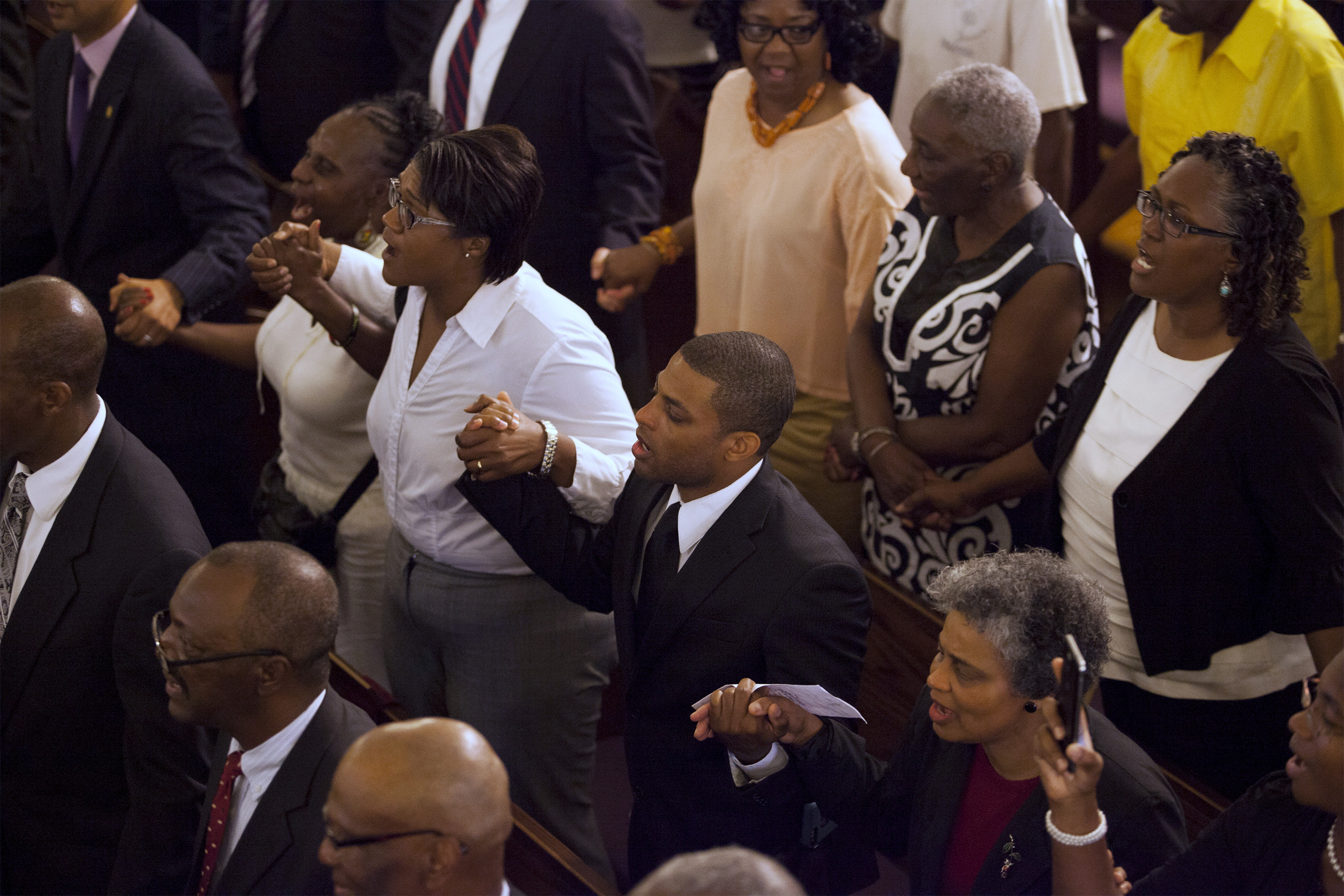 The congregation holds hands during a prayer service for Wednesday's shooting victim held at the Morris Brown AME Church in Charleston