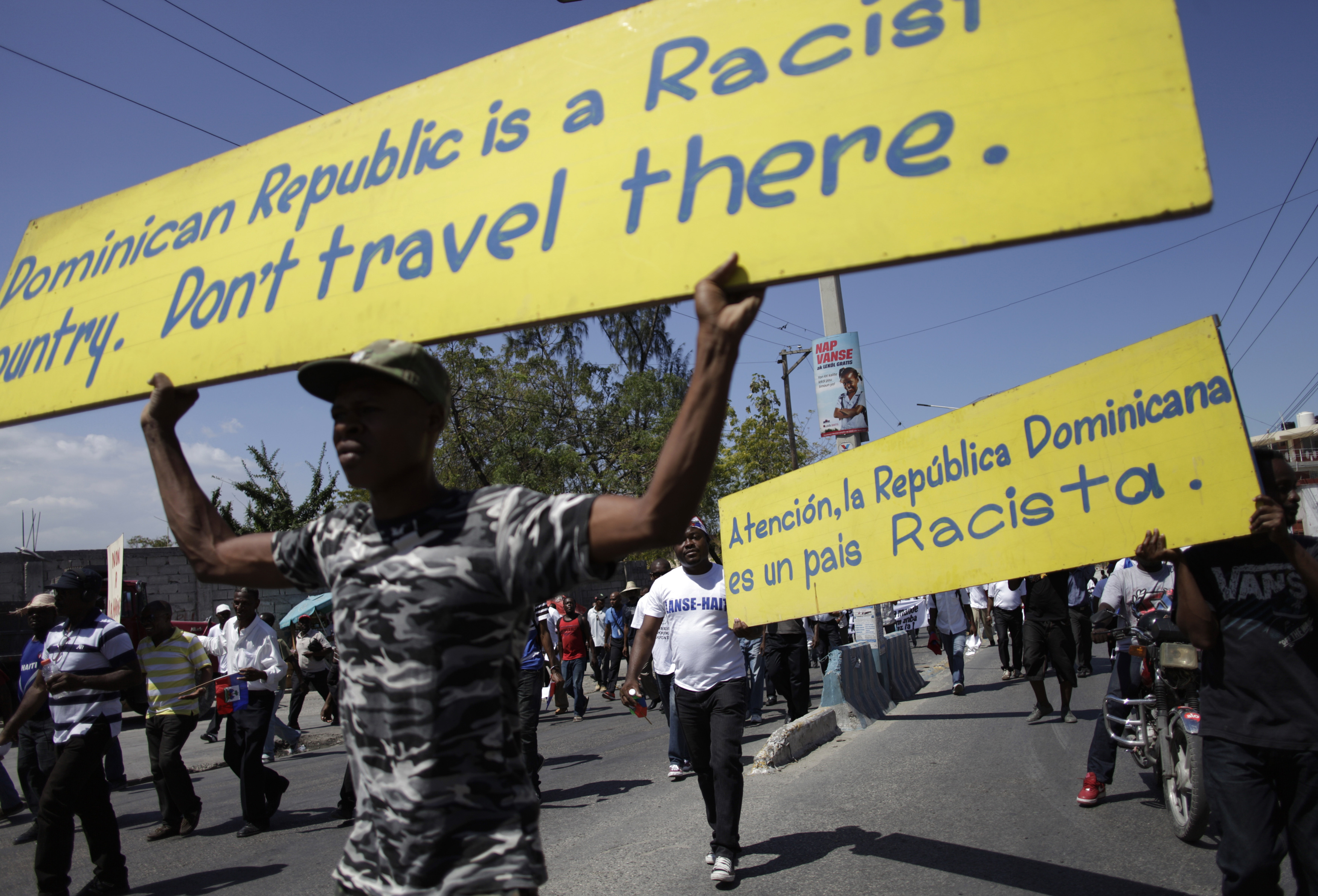 Protesters holds signs while marching on a street in Port-au-Prince