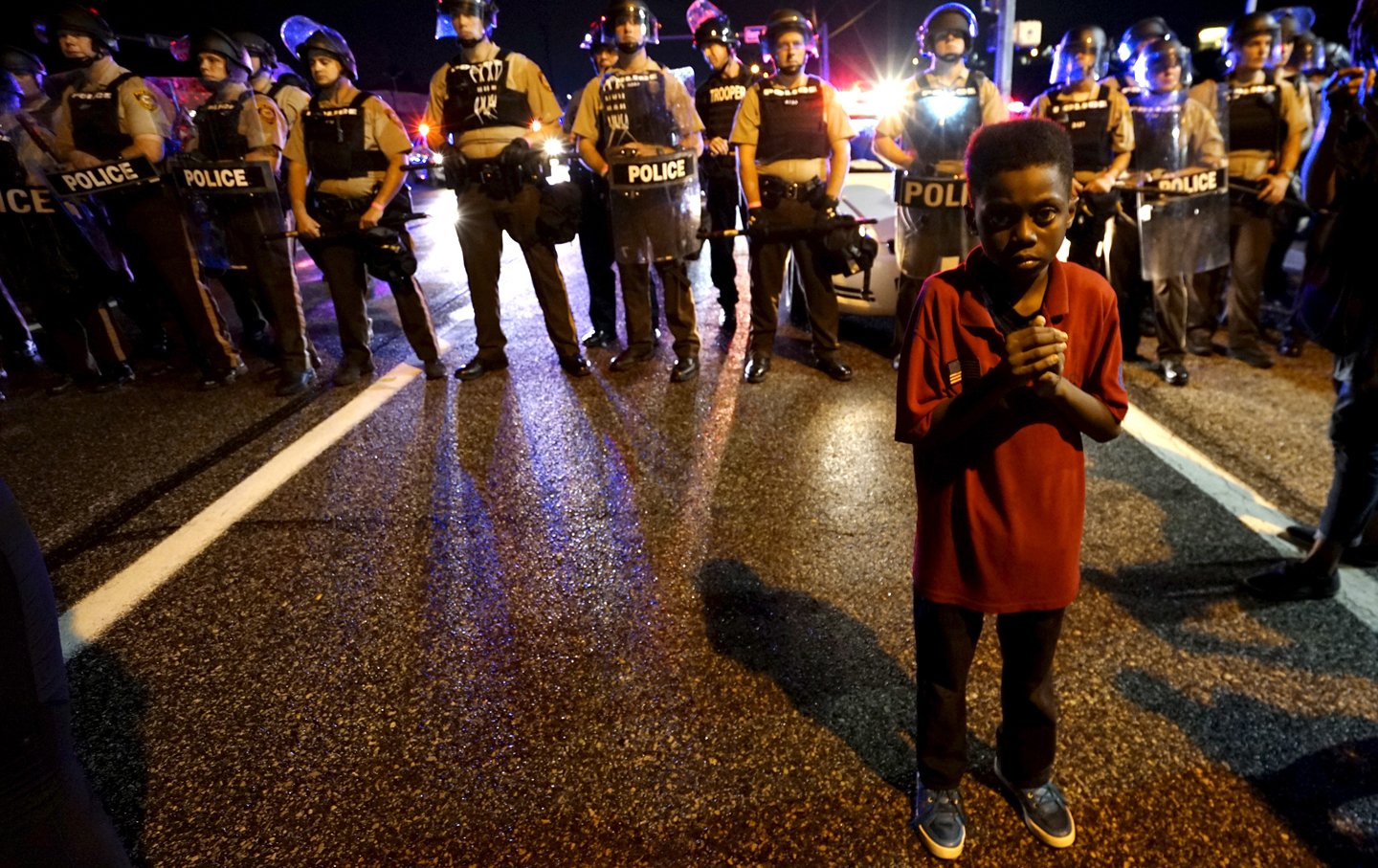Child stands in front of police