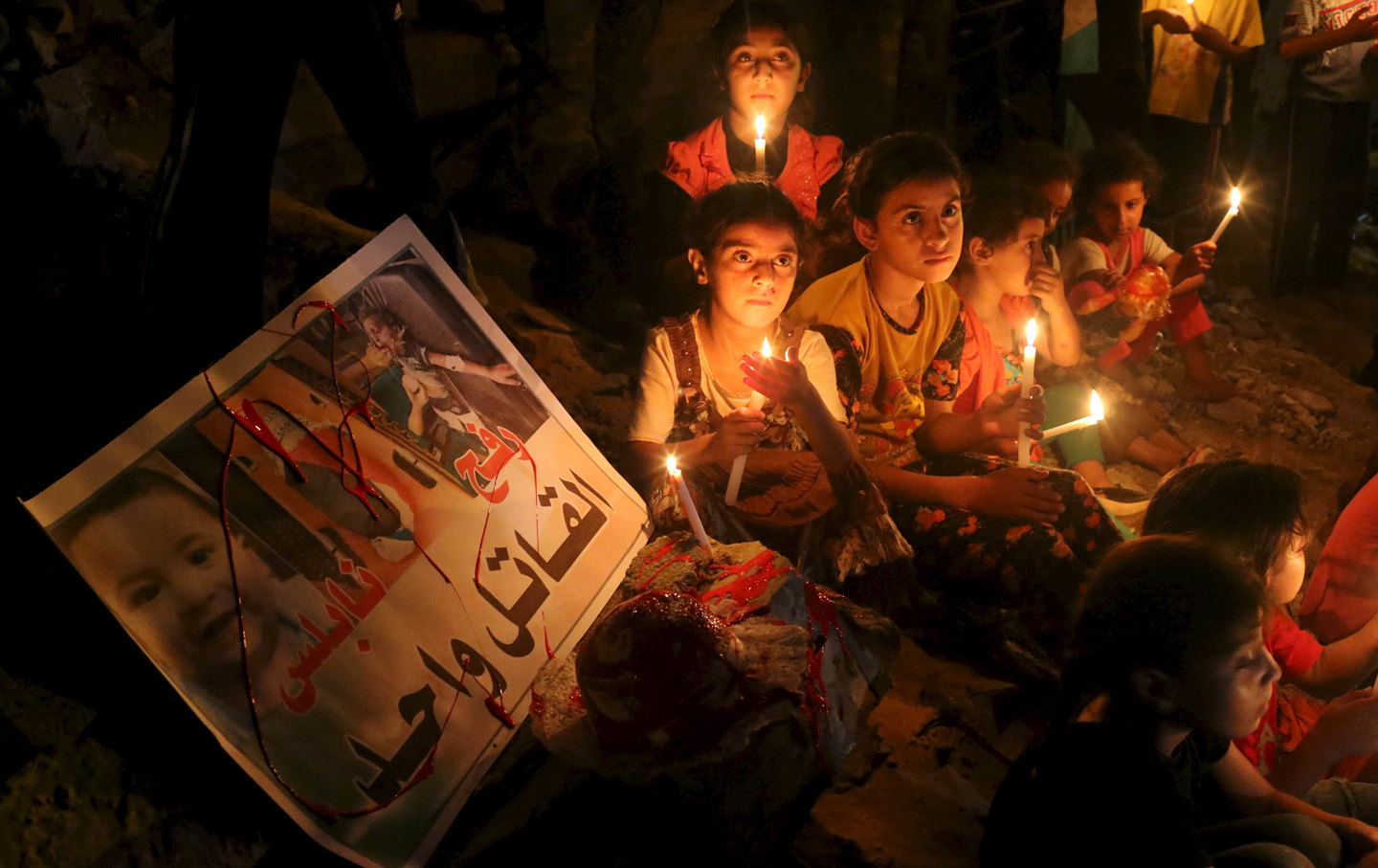Palestinian children light candles during a rally to remember 18-month-old Palestinian baby Ali Dawabsheh who was killed after his family's house was set on fire in a suspected attack by Jewish extremists in Rafah in the southern Gaza Strip