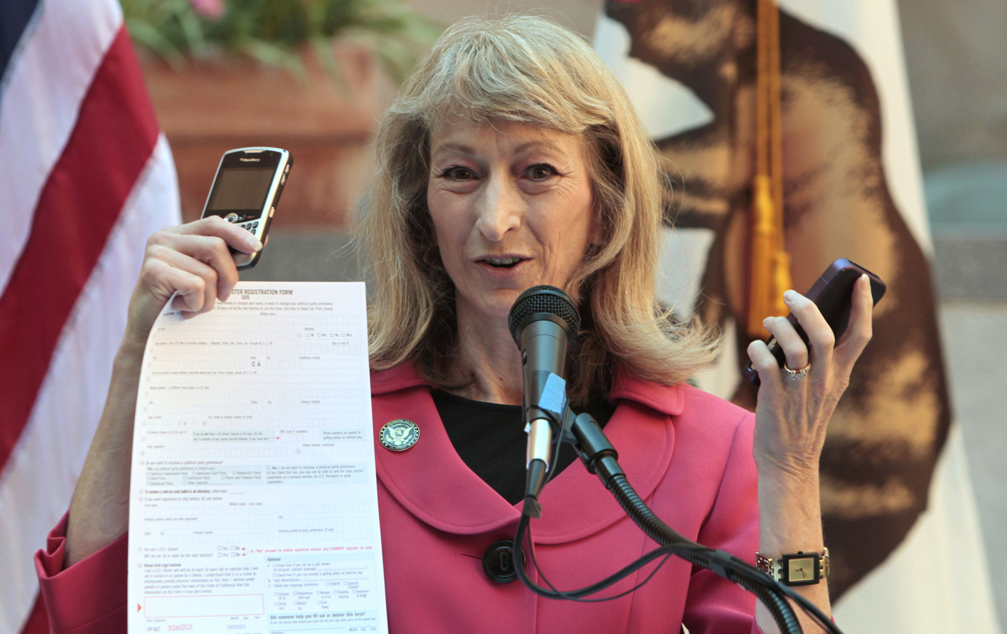 California Secretary of State Debra Bowen displays cellphones and a paper form following the signing of California's new online voter registration bill.