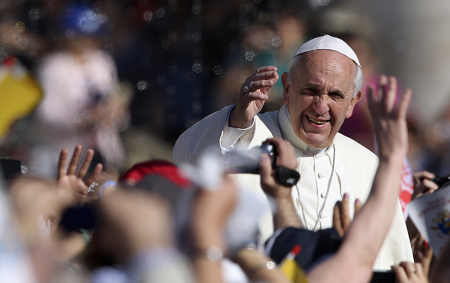 Pope Francis waves as he arrives to lead his Wednesday general audience in Saint Peter's square at the Vatican.