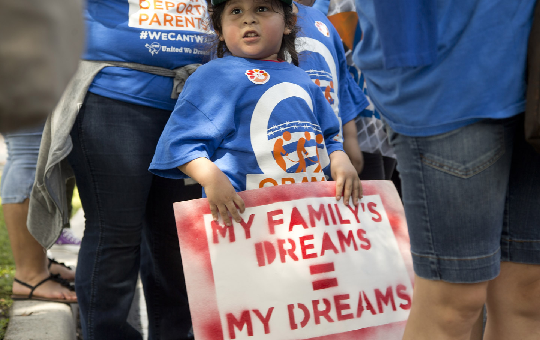 Miguel Nunez holds a sign demanding immigration reform in Deerfield Beach, Fla, Wednesday, Aug. 20, 2014.