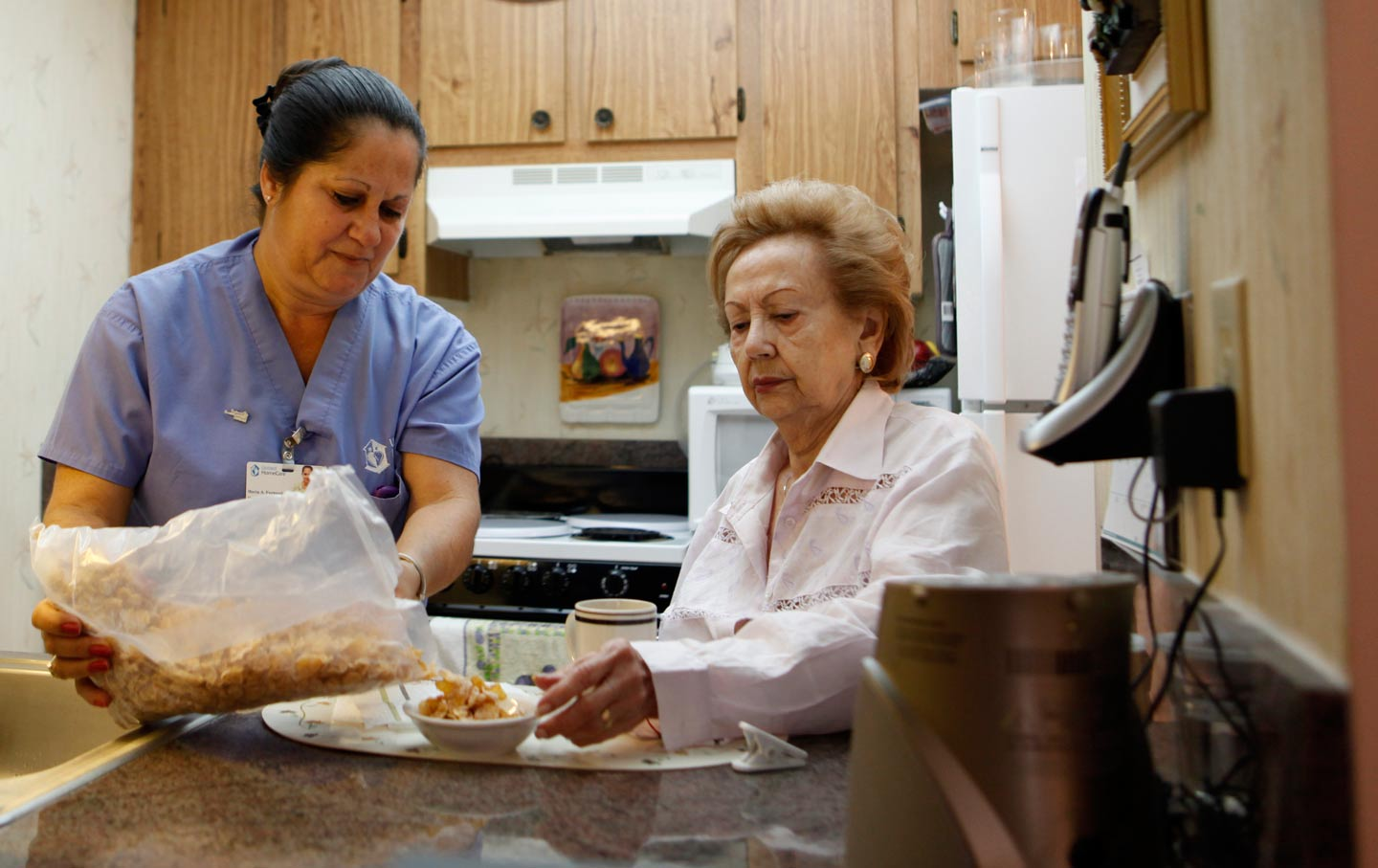home health aide Maria Fernandez, left, pours cereal for Herminia Vega, 83.