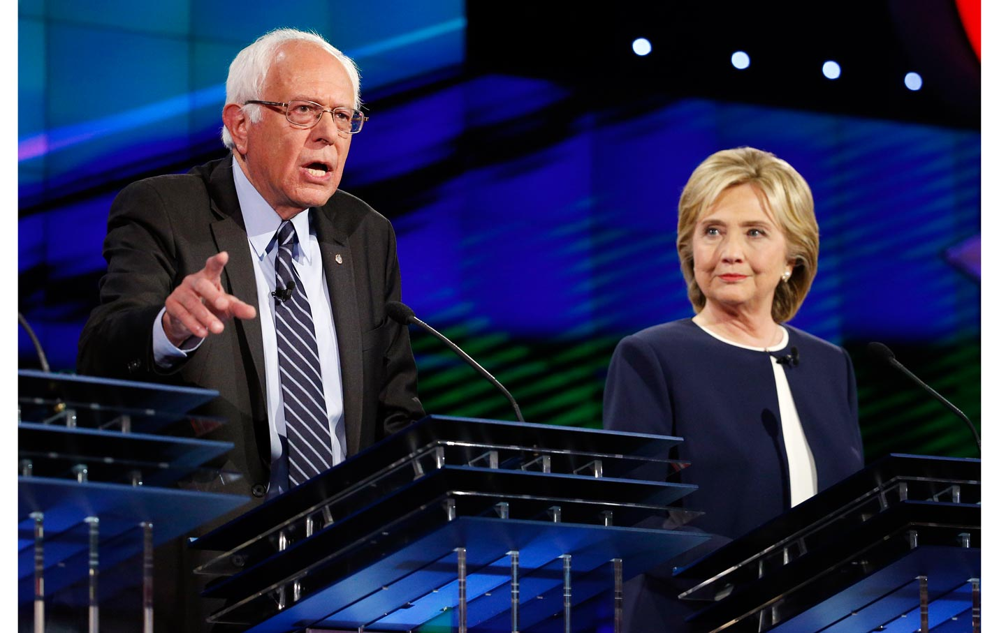 Clinton looks on as Sanders speaks during the Democratic debate on October 13, 2015.