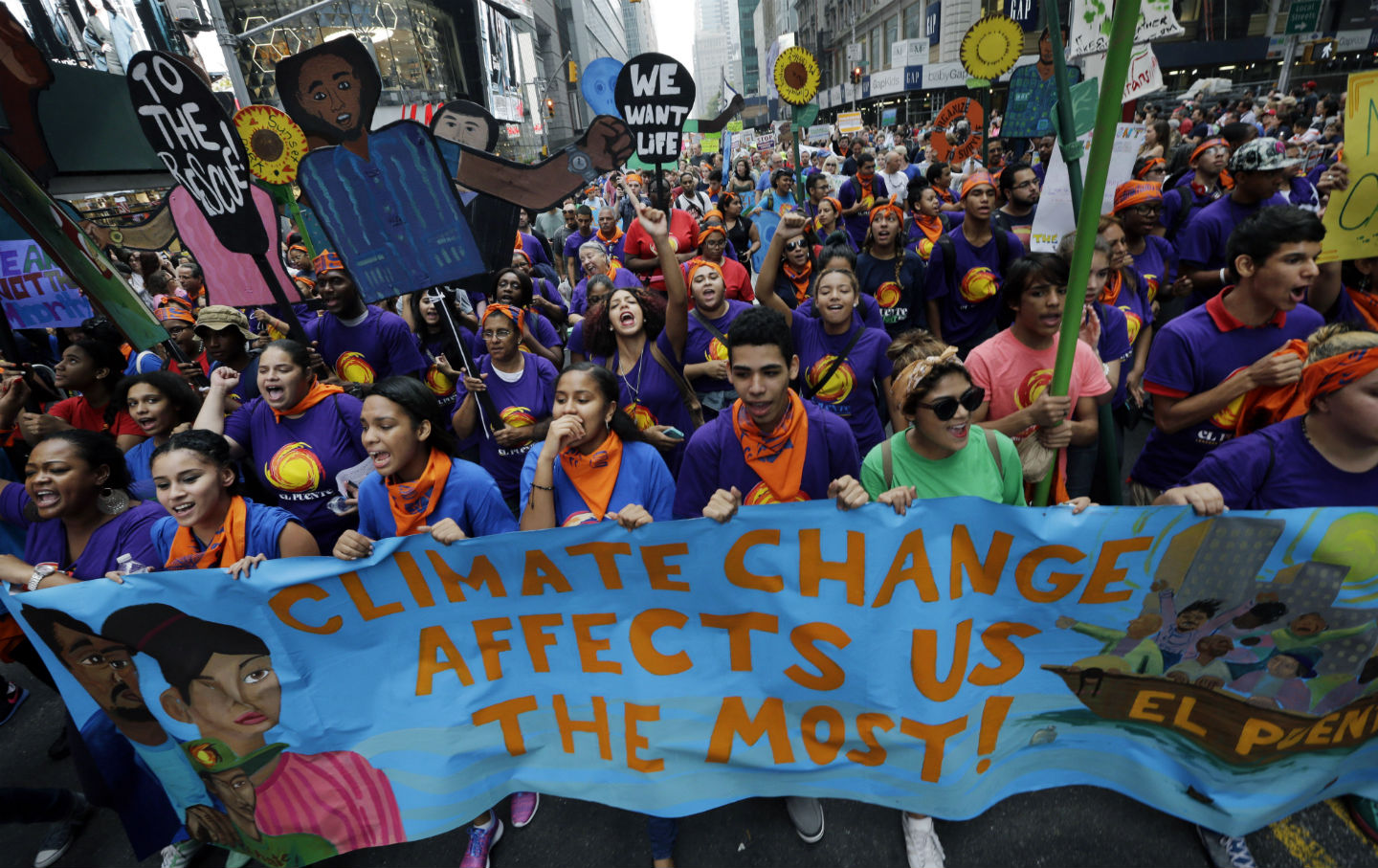 Young activists hold signs at the People's Climate March