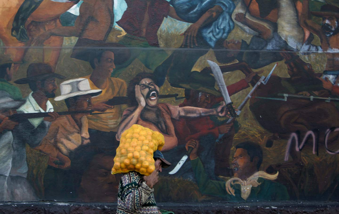 A man carries a sack of oranges while walking past a mural depicting a fight between farmers and private landlords in Tegucigalpa, Honduras's capital.