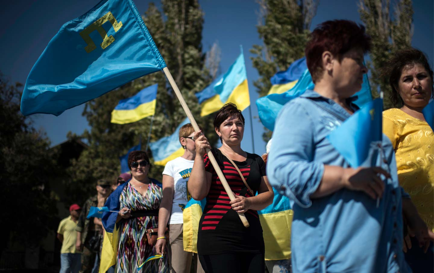 Local residents carry Ukrainian and Crimean Tatars flags in Chongar, Ukraine.  (AP Photo / Evgeniy Maloletka)