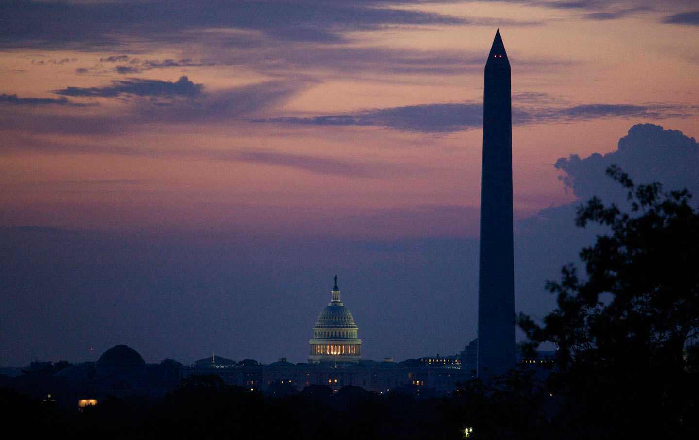 The Washington Monument and US Capitol silhouetted at dawn in Washington, DC.