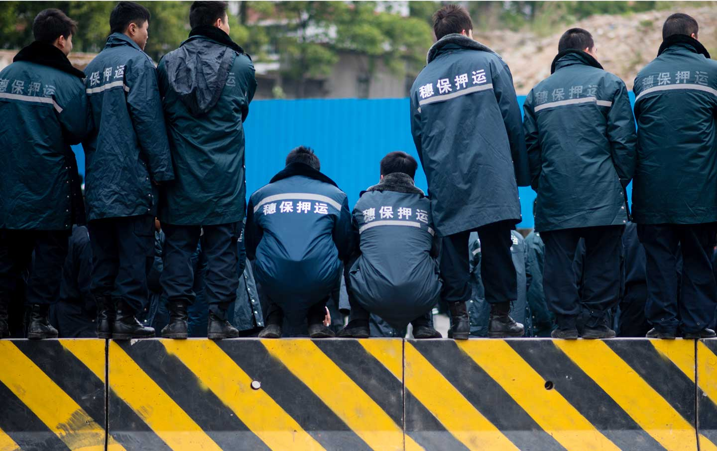 Workers of Sui Bao Security Transport Company strike for higher salaries, blocking a road in Guangzhou, China, February 11, 2014.