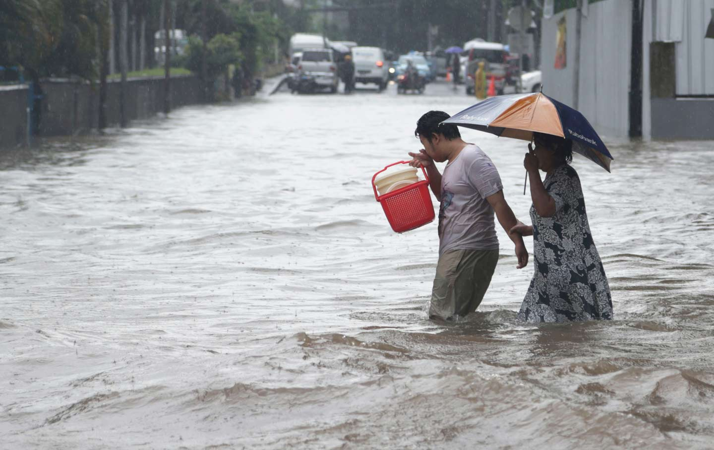 A couple wades through floodwaters in Jakarta, Indonesia.