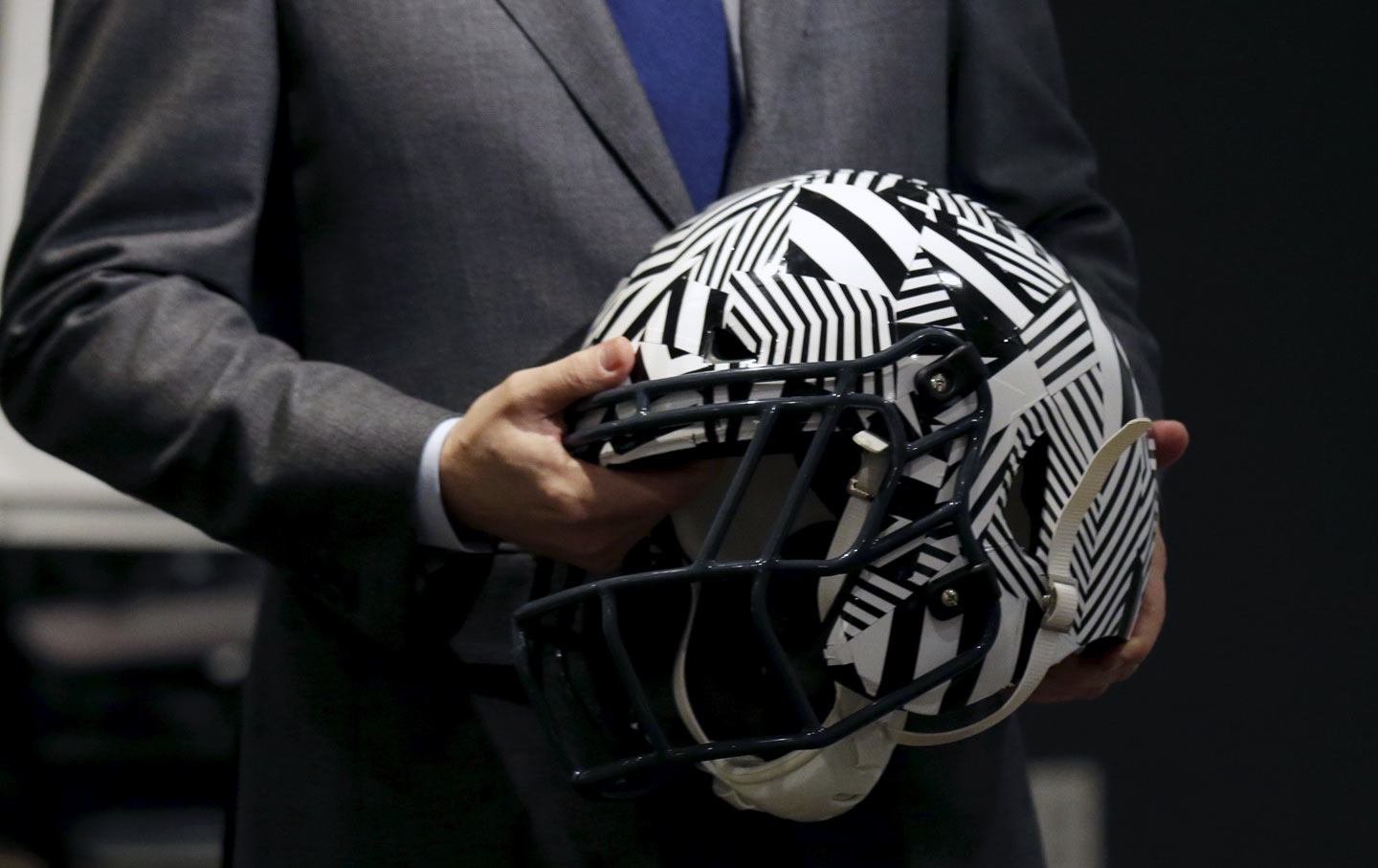 "A representative holds an ""impact-absorbing"" helmet at NFL Headquarters in New York."