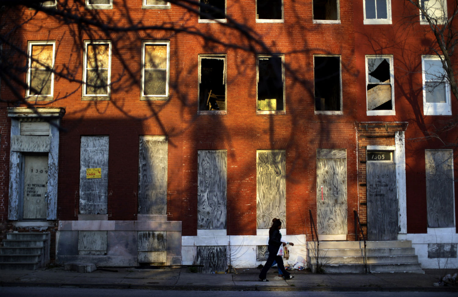 A woman walks past abandoned row houses in Baltimore, Maryland.