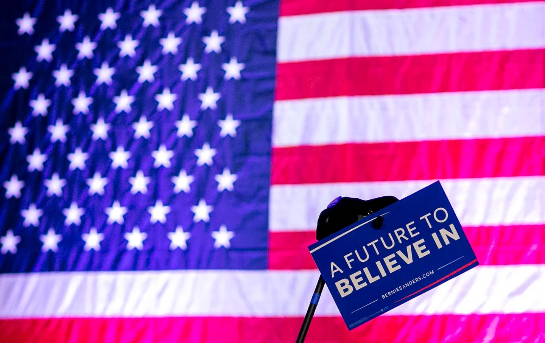 Bernie Sanders sign held in front of flag