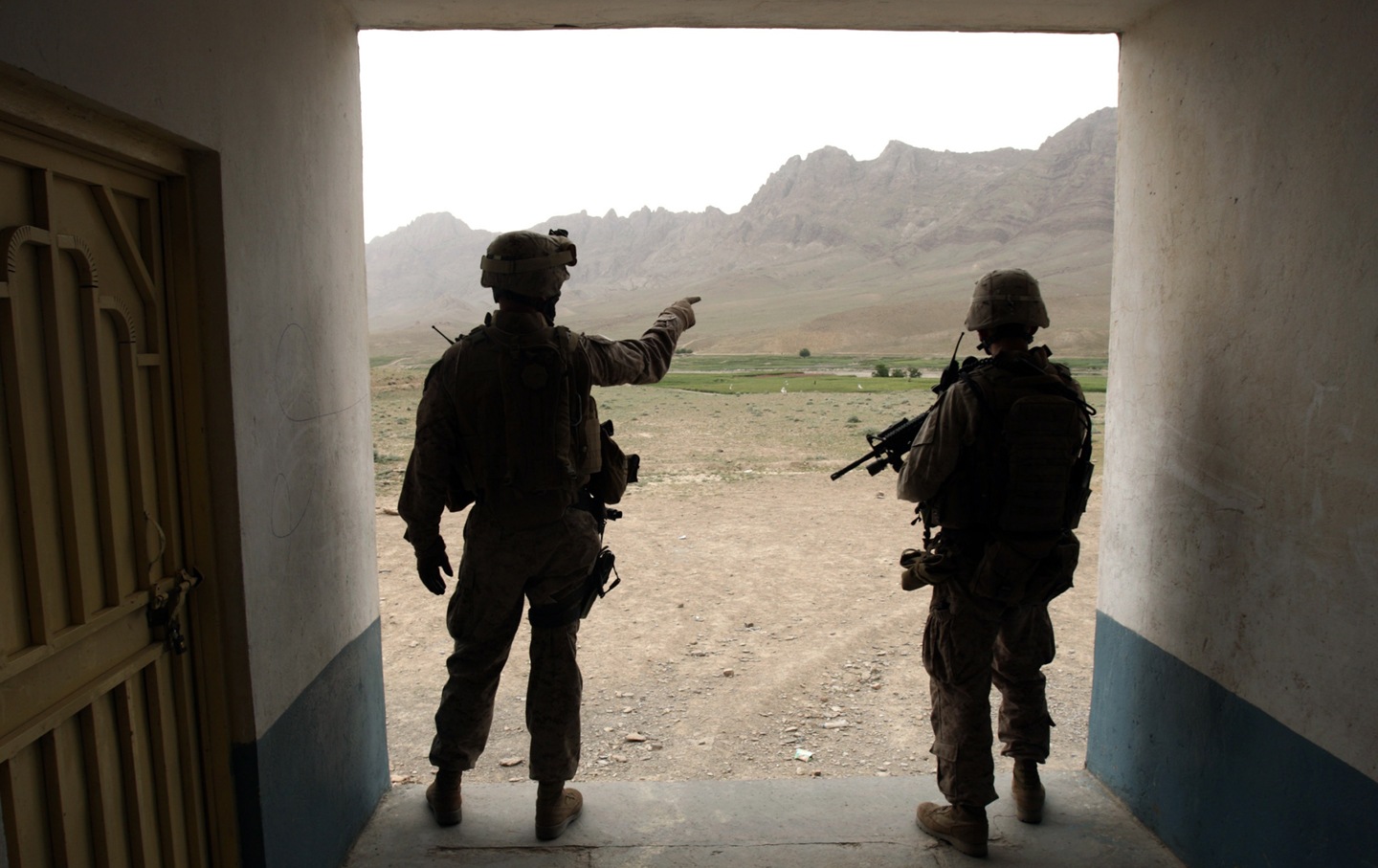 US Marines observe an area from a school building during a patrol at a village in the Golestan district of Farah province