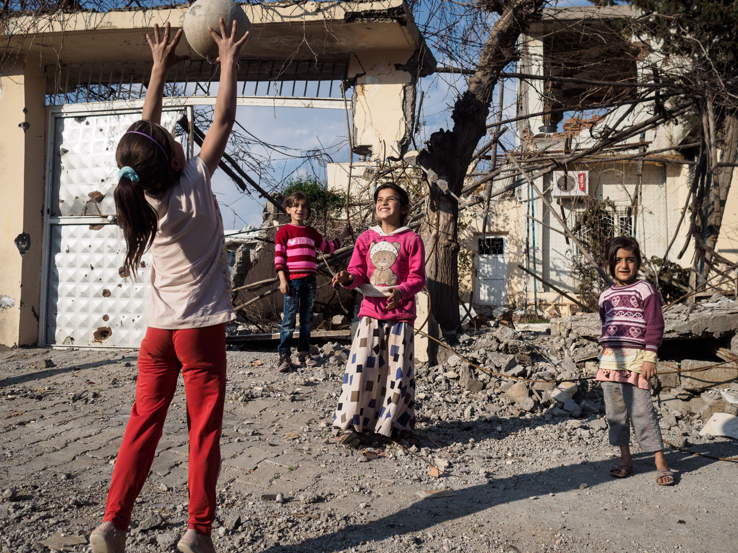 Children playing in front of their damaged house in Cizre.