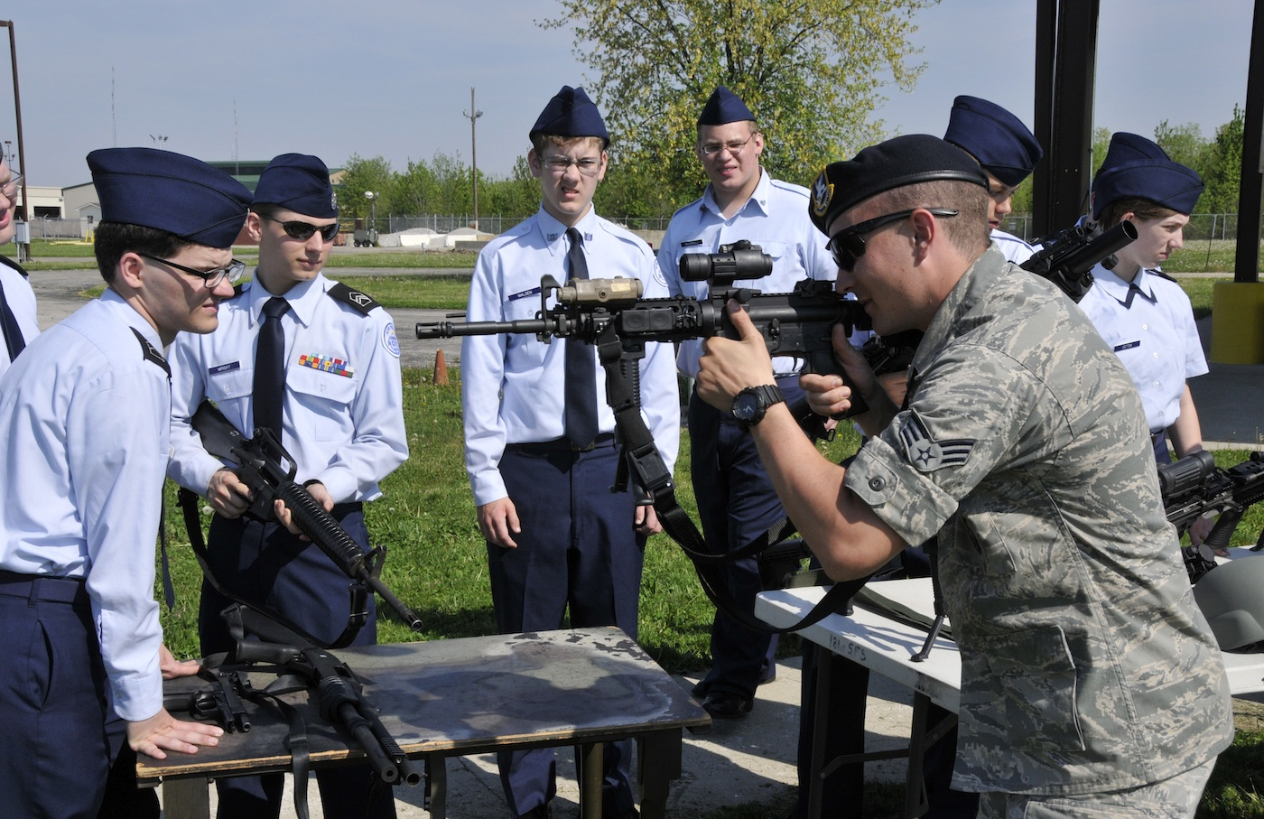 An airman in the United States Air Force demonstrates proper firing position while using the M4 rifle, with students from Terre Haute North High School in Indiana on May 6, 2015. (US Air National Guard photo by SMSgt. John S. Chapman / Released)