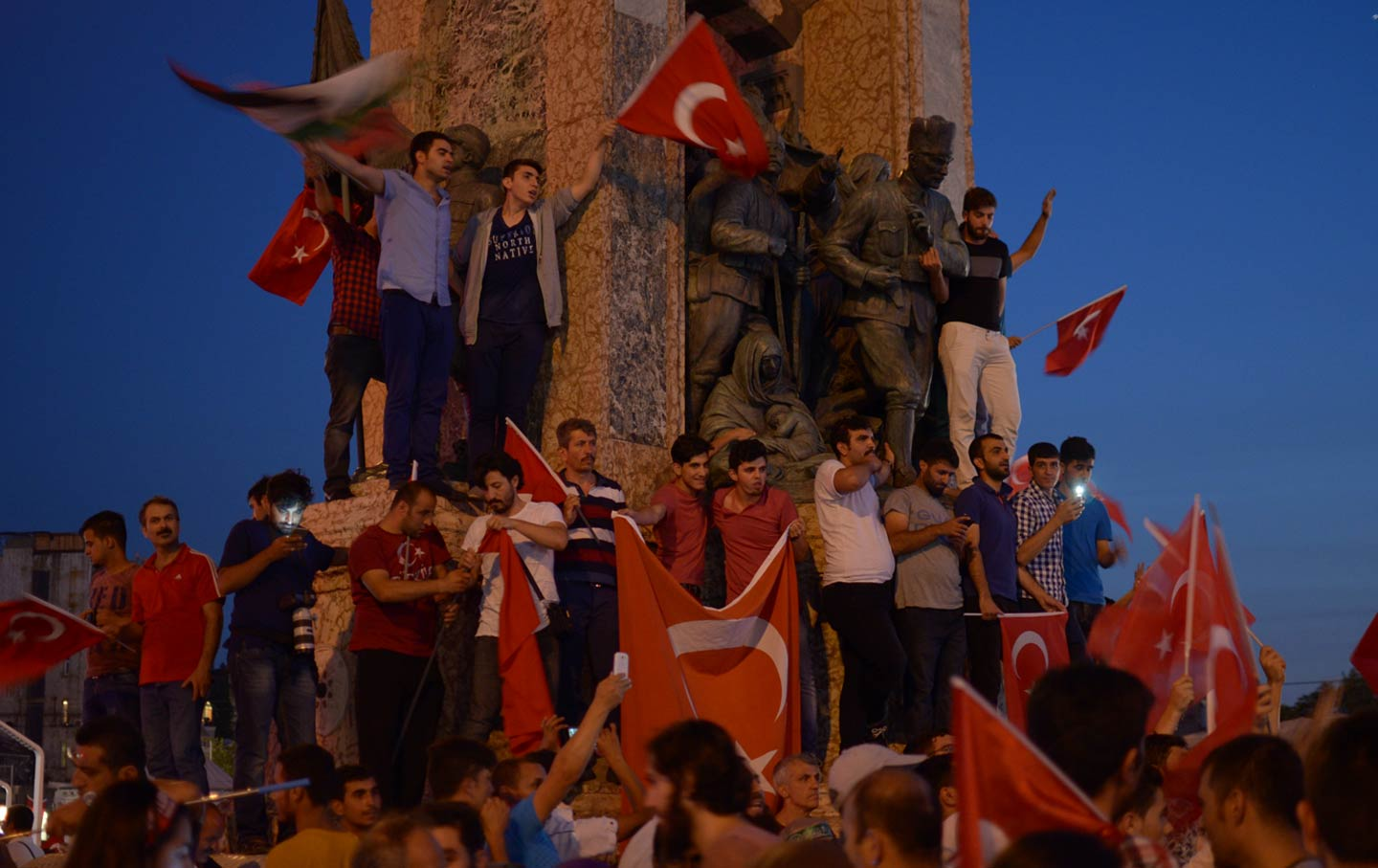 Young men stand on the statue of Mustafa Atatürk, the founder of Turkey who instituted secular democracy.