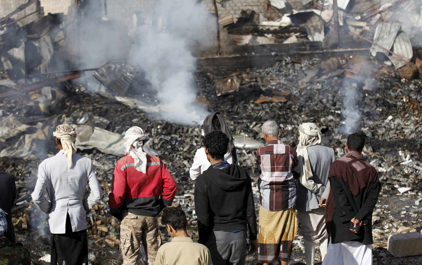 Civilans look at rubble from Saudi airstrike