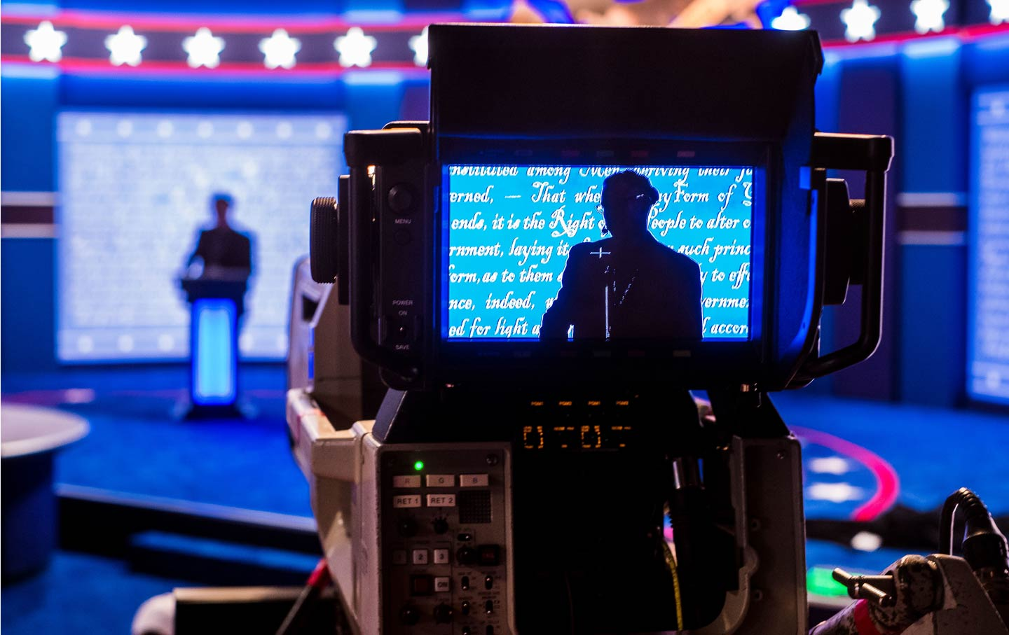 Person in monitor on debate stage