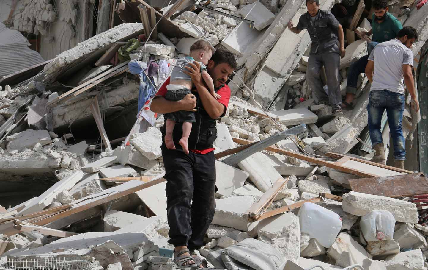 man carrying injured child from rubble