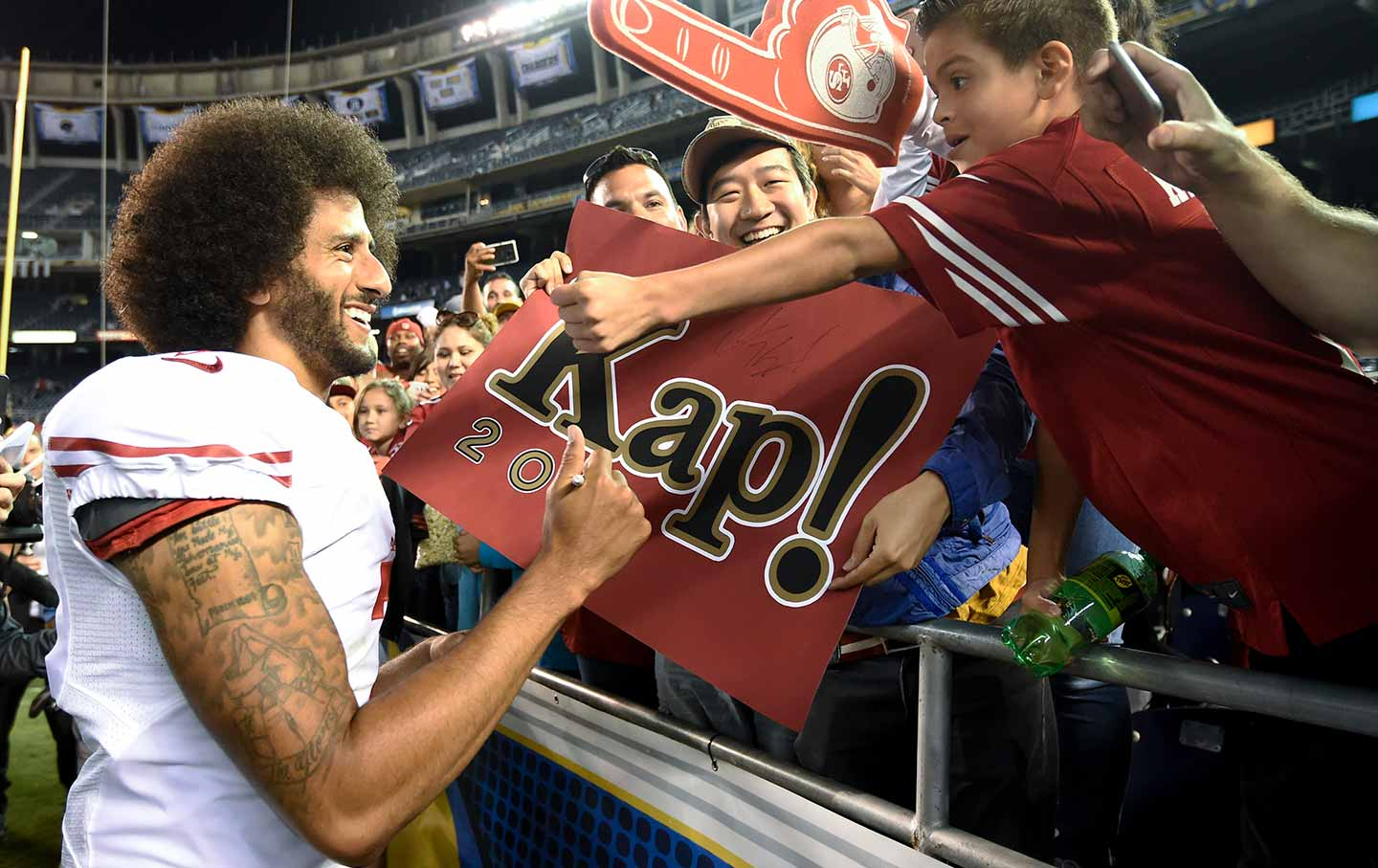 Colin Kaepernick greets fans after a preseason game (AP Photo / Denis Poroy).