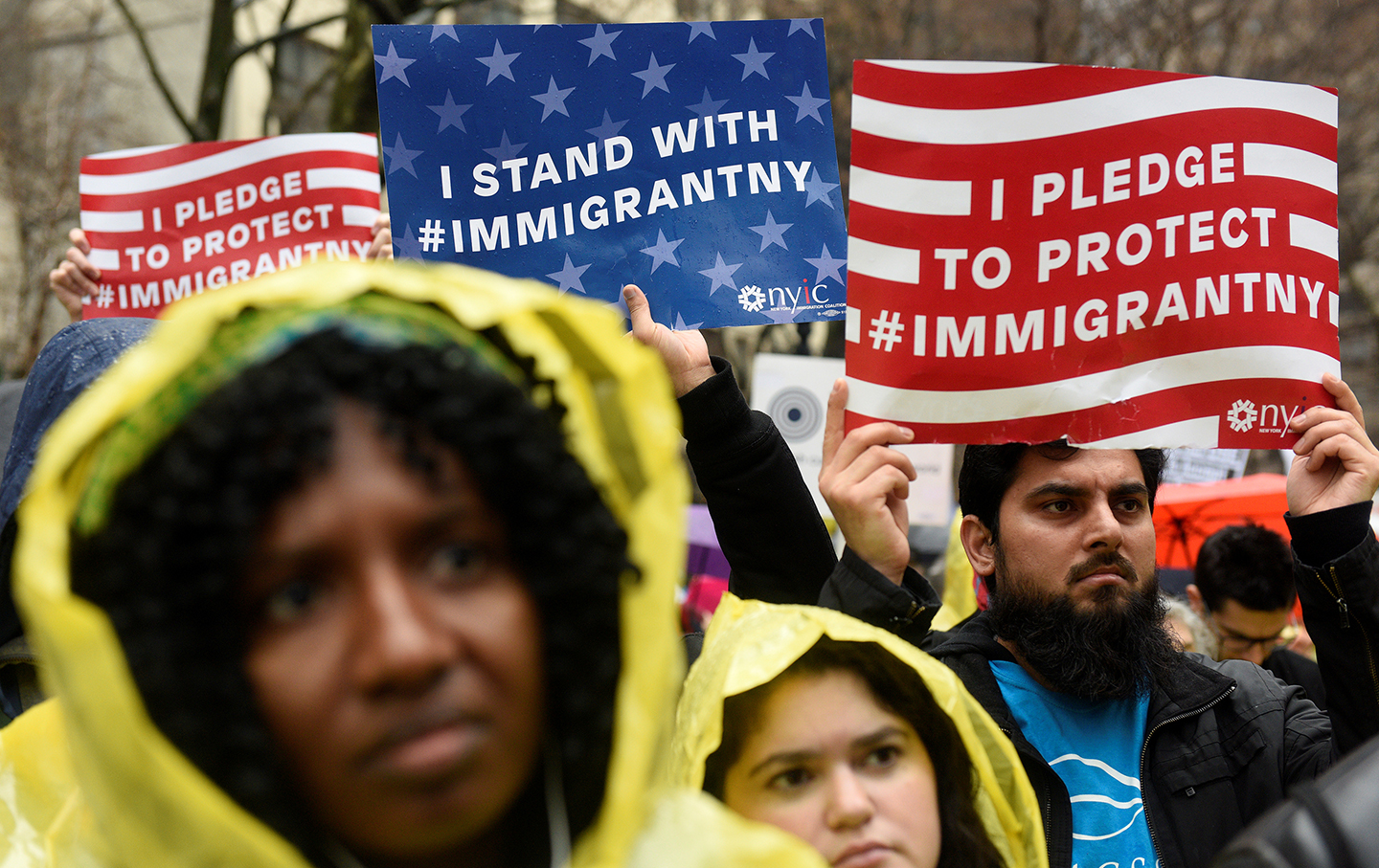 People hold up signs at an immigration rally