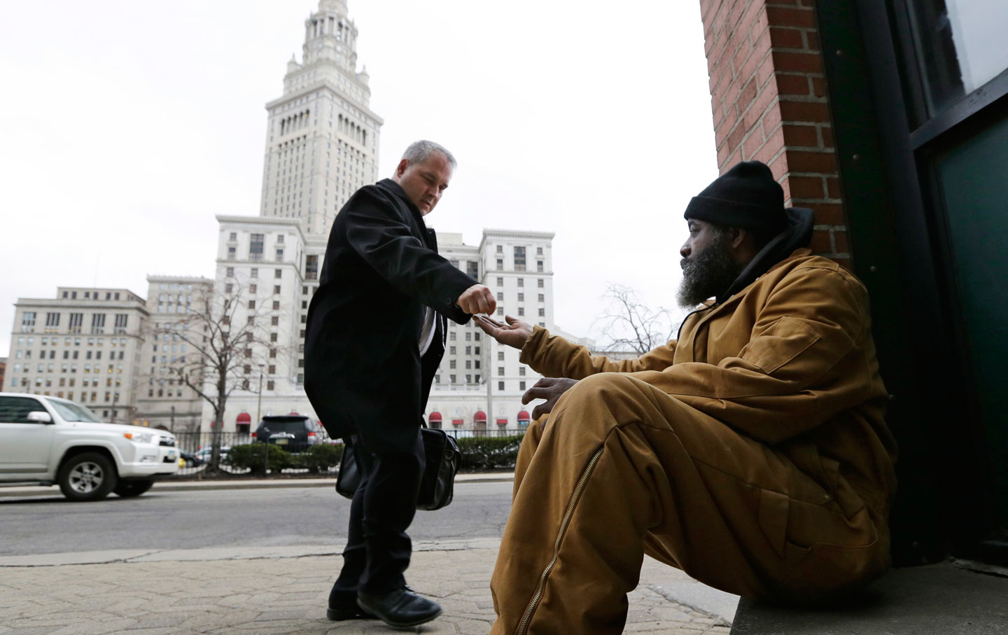 Kenny Chapman, 53, receives coins from a man