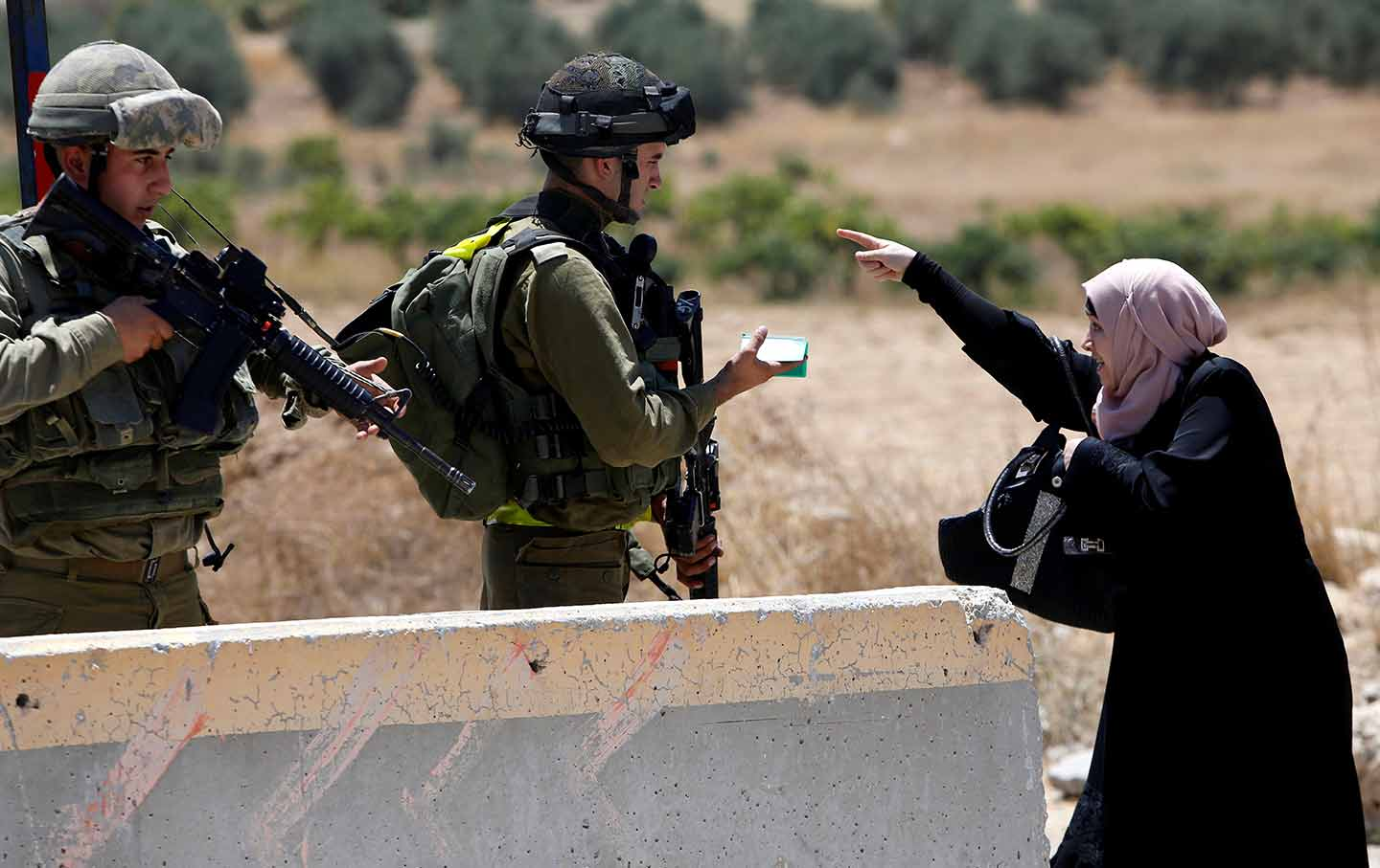 A Palestinian woman argues with Israeli soldiers at a West Bank checkpoint south of Hebron on August 16, 2016. (Reuters / Mussa Qawasma)