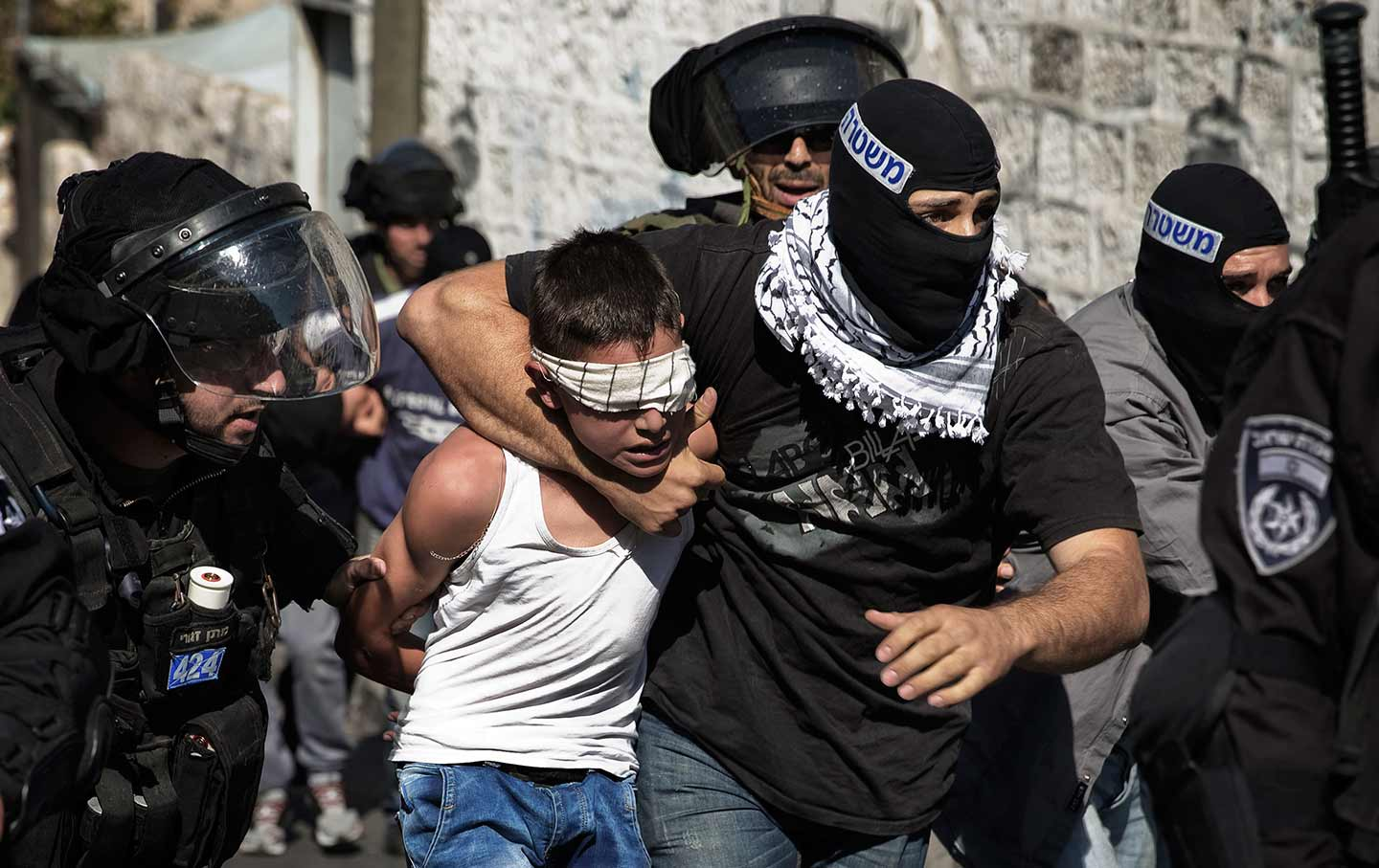 A Palestinian child is taken by Israeli police in Jerusalem