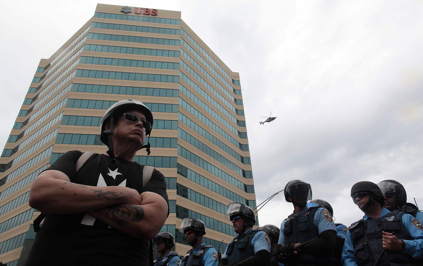 A Demonstrator Stands Near Police Officers During Protest Against The Government S Austerity Measures In San Juan Puerto Rico May 1 2017