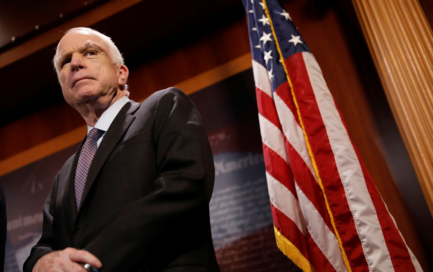 Senator John McCain looks on during a press conference
