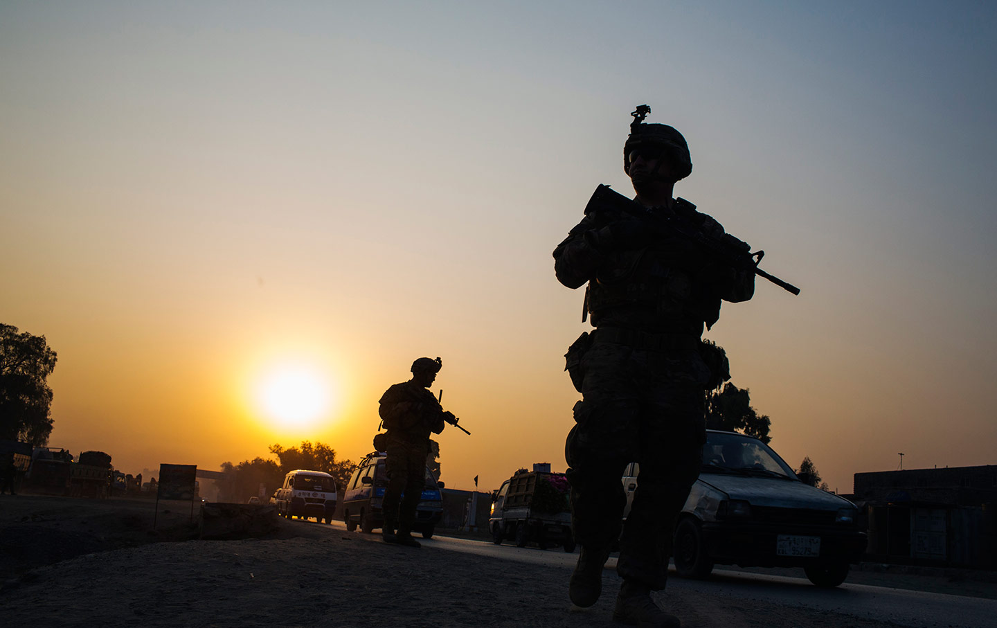 US soldiers walk near a police checkpoint in Afghanistan